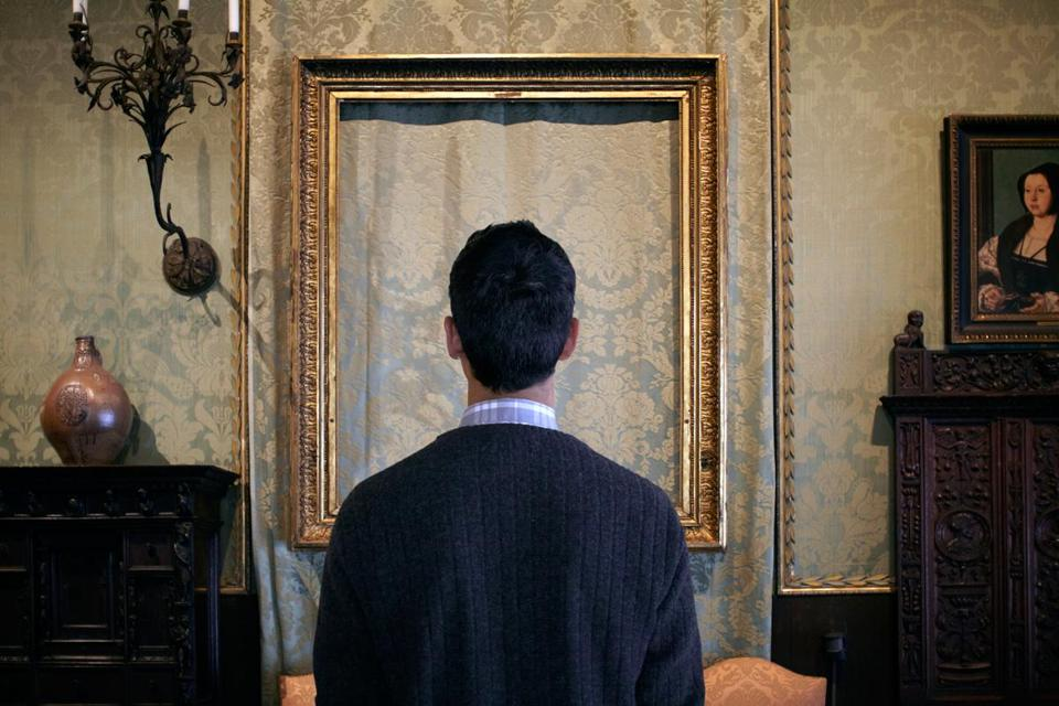 "In one of Sophie Calle's images for ""Last Seen,"" a man looks at the space where a Rembrandt once hung at the Gardner."