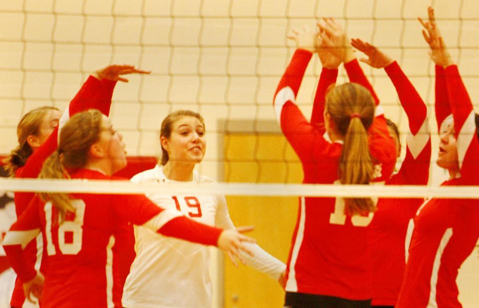 The Melrose High girls volleyball team celebrates after a point in a Middlesex League matchup against Burlington High School.