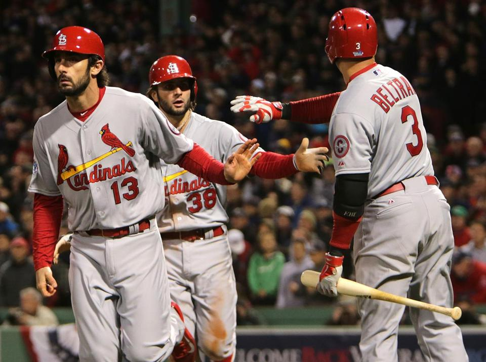 Matt Carpenter, left, and Pete Kozma were congratulated by Carlos Beltran after scoring in the seventh inning.