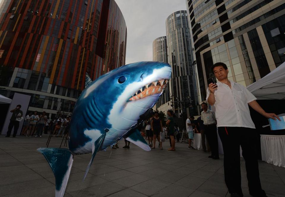"A man photographed an inflatable toy shark during a ""No Shark Fin"" campaign in Beijing in August. It was organized by Jane Goodall's Roots and Shoots conservation group."