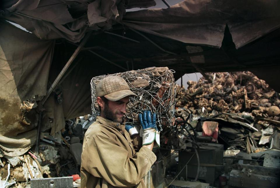 A man at a scrap yard near Bagram, Afghanistan, carried wires from US military bases.