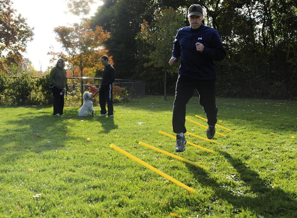 Charlie Bourke of Waltham did an obstacle course while his dog Jameson waited for him with dog trainer Joy Wrolson (left) and Mike Harb.
