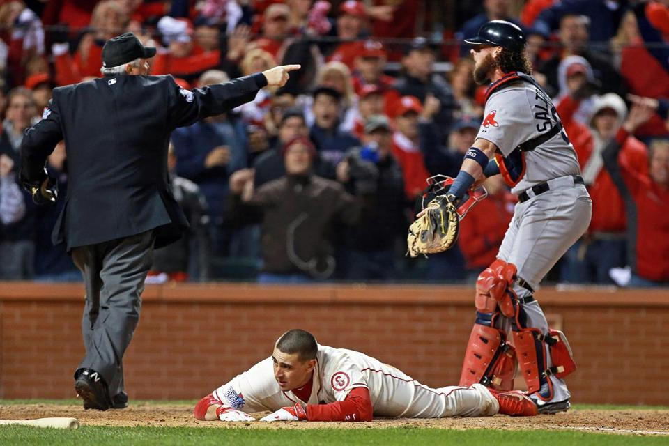 Sox catcher Jarrod Saltalamacchia pleads his case, but plate umpire Dana DeMuth is already signaling that the Cardinals' Allen Craig is safe because of obstruction at third base.
