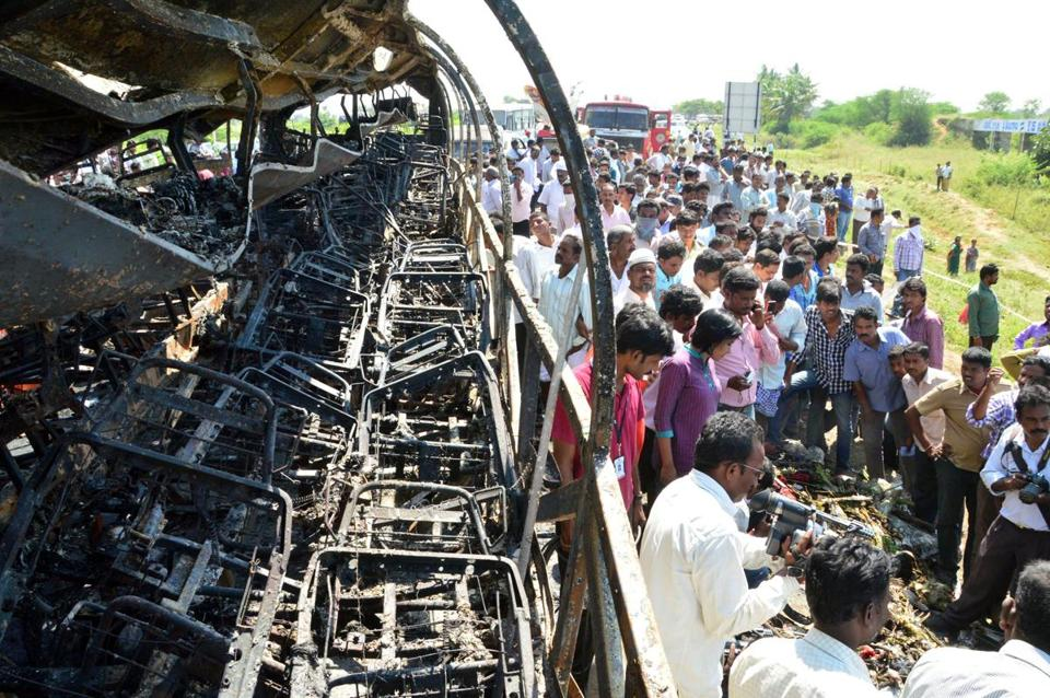 People gathered near the remains of a bus that crashed and caught fire in southern India. Seven people escaped.