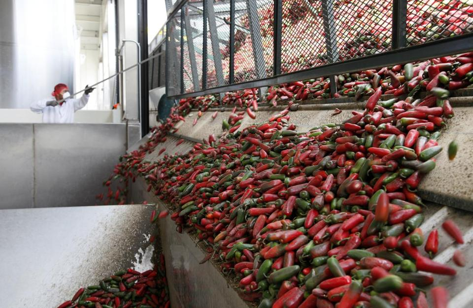 A worker unloaded chilis used to make Sriracha sauce in Irwindale. Fumes bother some residents' eyes and throats.