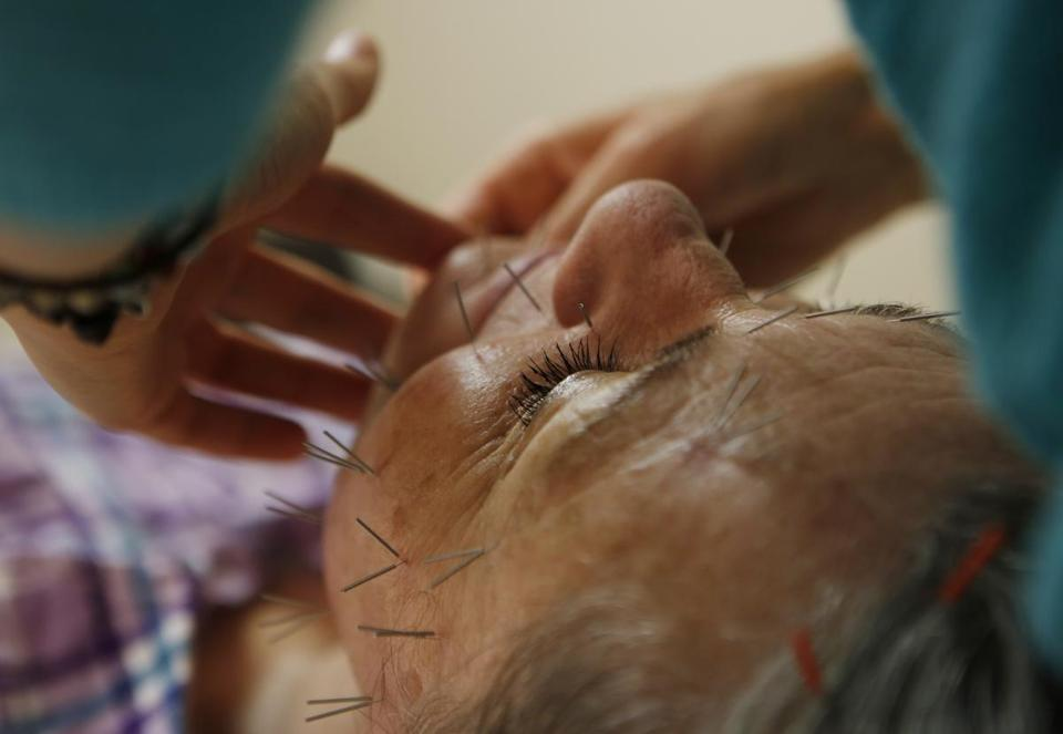 Beverly resident Lora Lipman is in the hands of  acupuncturist Stephanie Kula during a recent treatment.