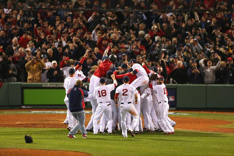 The Red Sox celebrate after winning the World Series, trouncing the St. Louis Cardinals 6-1 at Fenway Park.