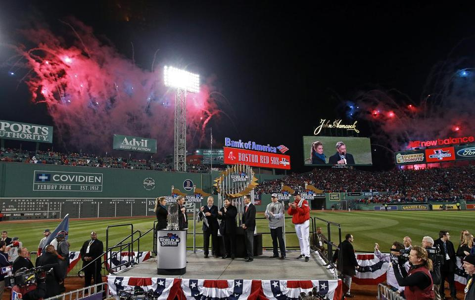 The skies light up as Bug Selig presents the championship trophy to Larry Lucchino, Tom Werner, John Henry, Ben Cherington, and John Farrell.