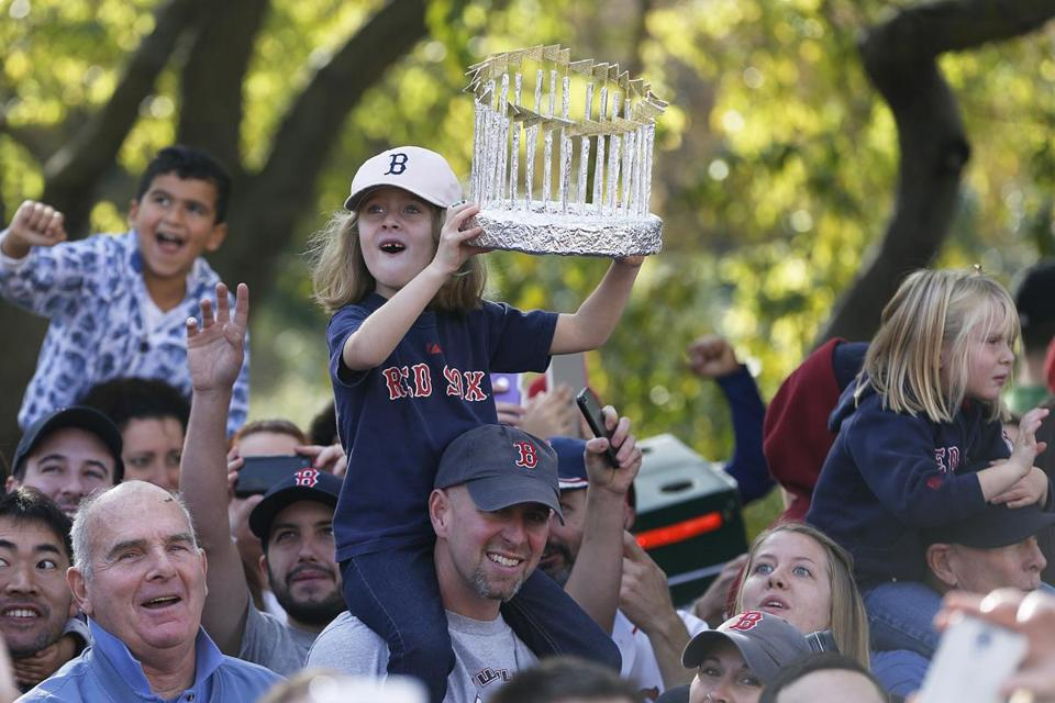 A girl held up a replica of a World Series trophy along the parade route in Boston.
