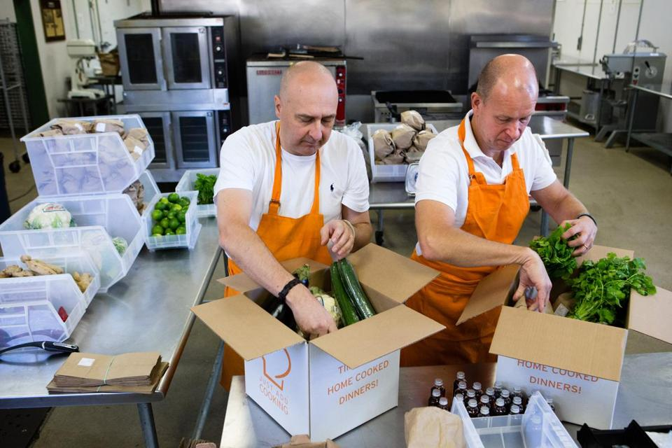Anders Lindell (left) and Jan Leife, founders of Just Add Cooking, pack up the meal boxes, including spices, at the industrial Crop Circle Kitchen in Jamaica Plain.