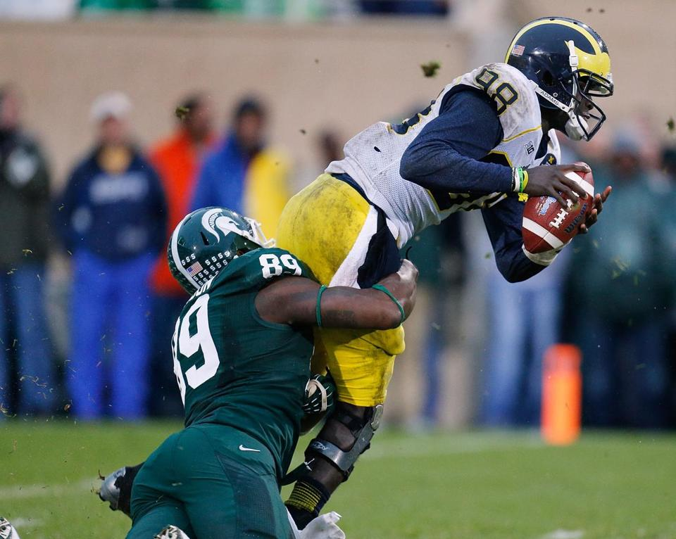 Michigan State's Shilique Calhoun pulls down Michigan QB  Devin Gardner, one of seven sacks by the Spartans.