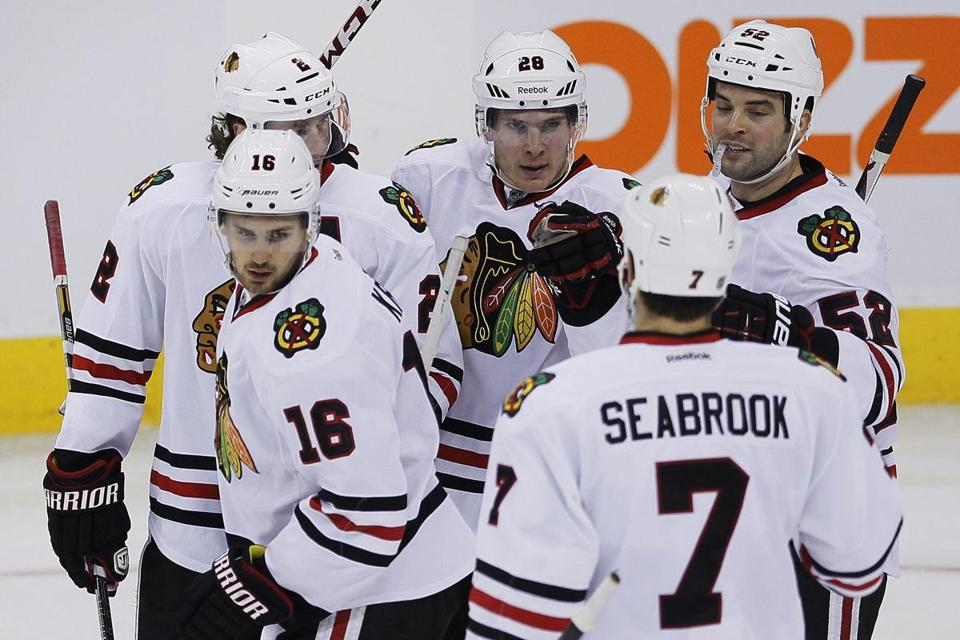 Chicago's Ben Smith (center) celebrates with teammates following his third-period goal.
