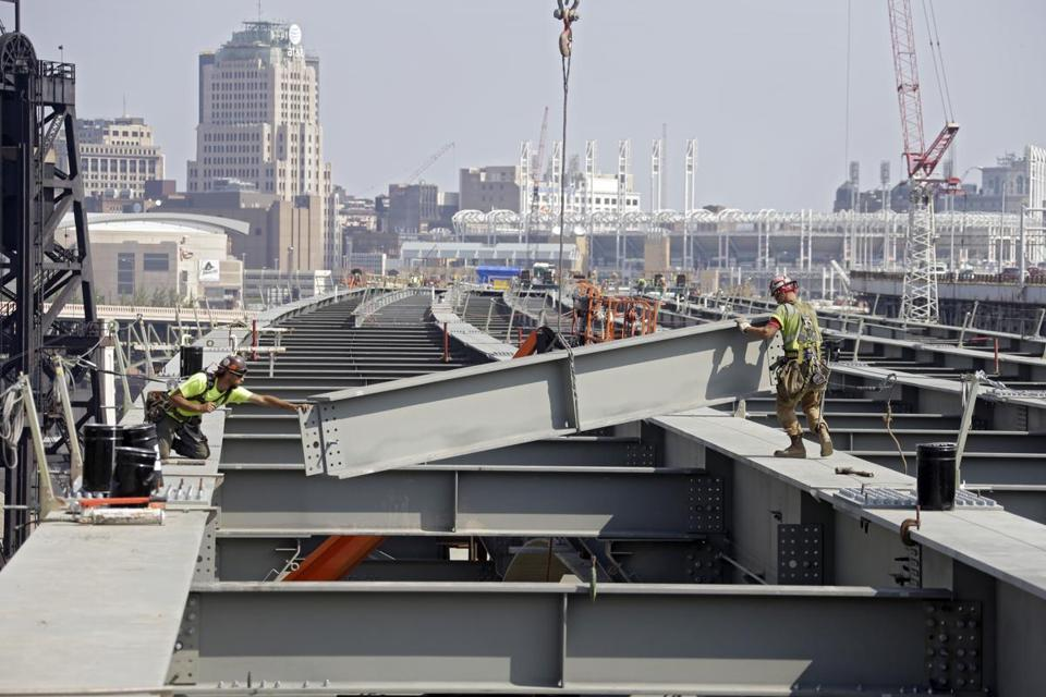 Workers guided a steel beam into place on a bridge under construction in Cleveland.