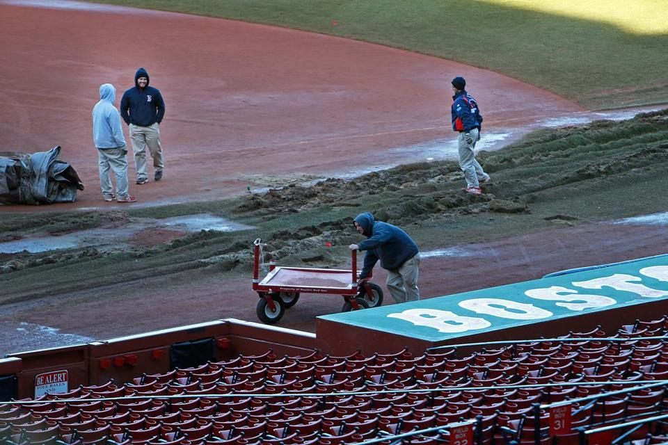 The grounds crew at Fenway works on repairing the ruts in foul territory left by the duck boats from Saturday's parade.