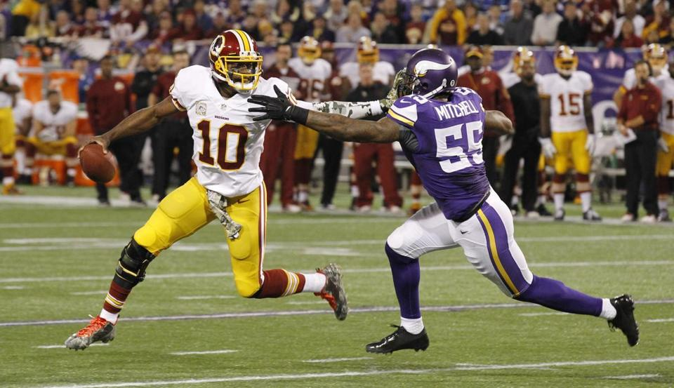 Robert Griffin III tried to break a tackle by Marvin Mitchell during the first half of Thursday's game.