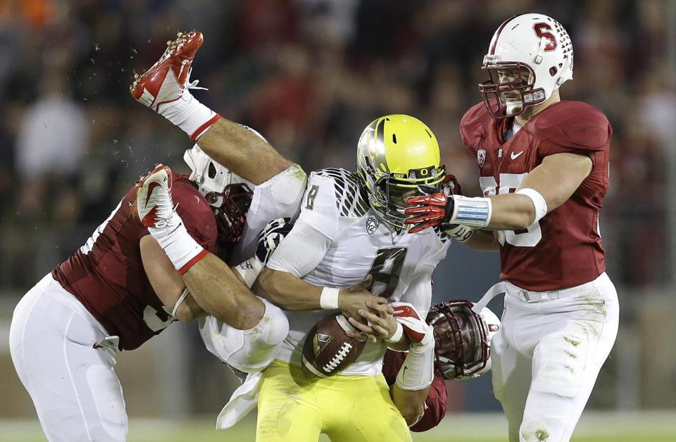 Oregon quarterback Marcus Mariota loses the ball as he's aggressively taken down by a trio of Stanford defenders in the third quarter.