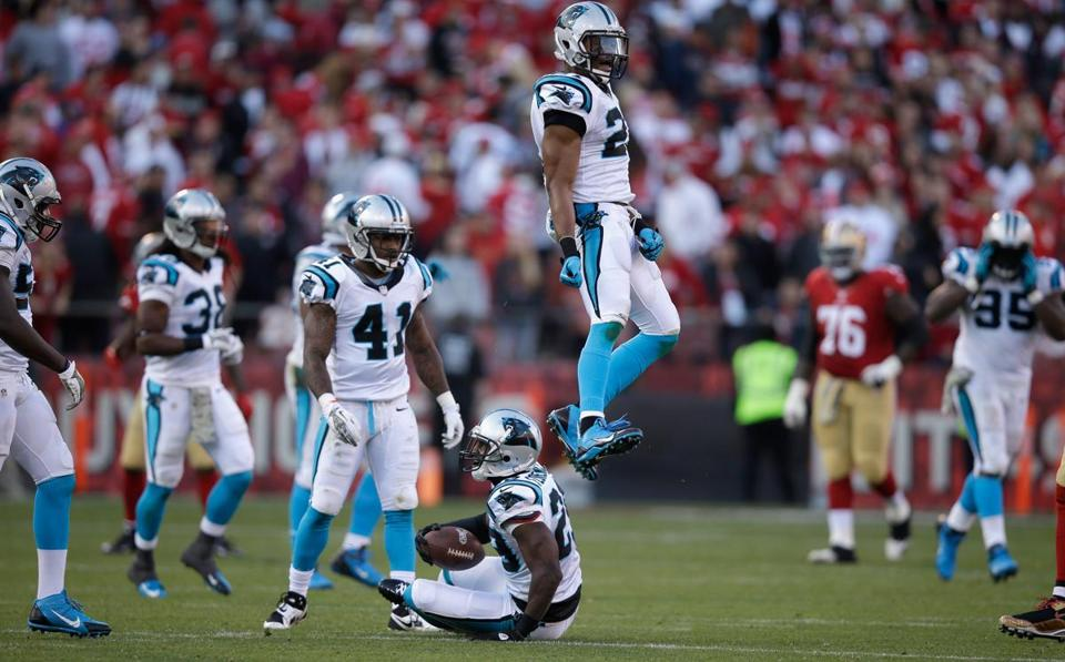 A game-sealing interception by Drayton Florence (seated) sent Panthers teammate Mike Mitchell (right) through the roof.