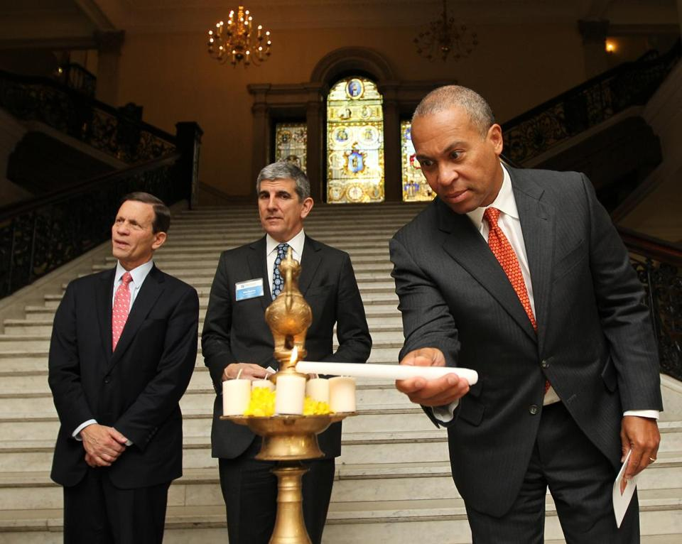 Governor Deval Patrick lit the diya during a State House Diwali ceremony. Also participating are Treasurer Steve Grossman (left) and MassMutual's Mike Fanning.
