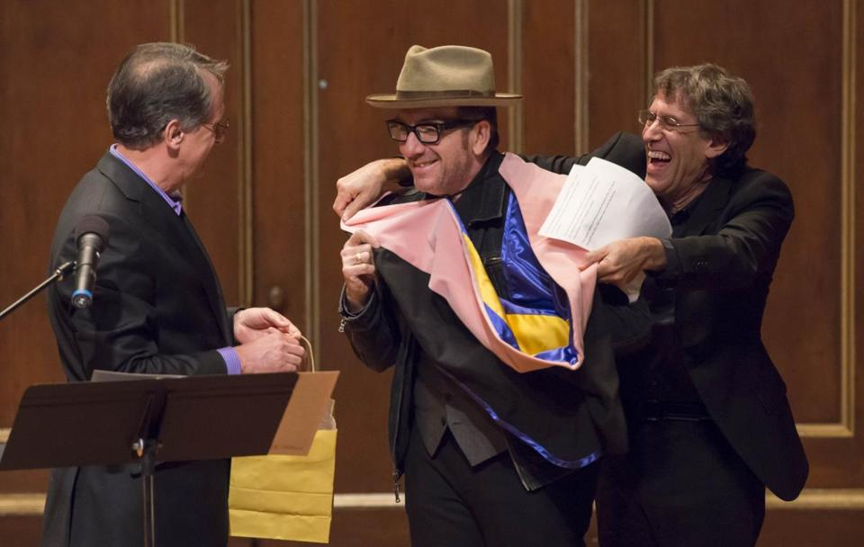 Tony Woodcock looks on as Hankus Netsky puts a robe on Elvis Costello during his honorary degree ceremony.