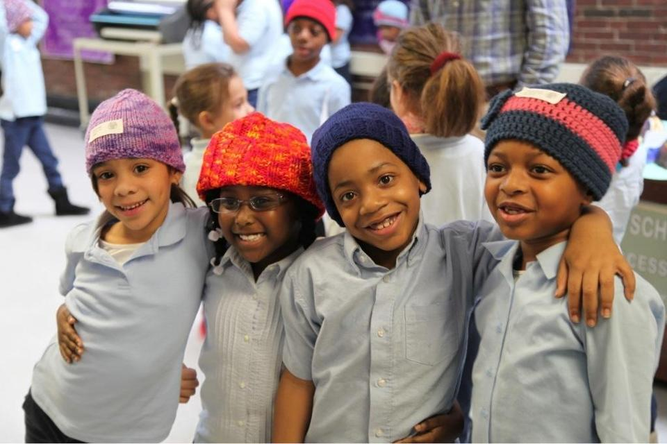 Students at the Tobin School in Boston wear hats from Caps for Kids.