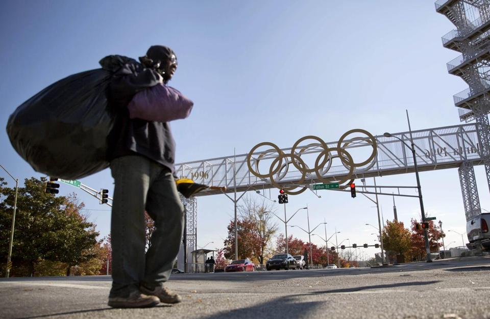 A pedestrian passed in front of the Olympic rings up the street from Turner Field, which originally opened as the 85,000-seat main stadium for the 1996 Olympics.