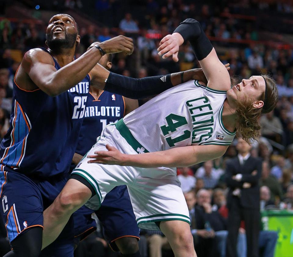 Kelly Olynyk of the Celtics bent over as he battled for position under the boards with Charlotte's Al Jefferson.