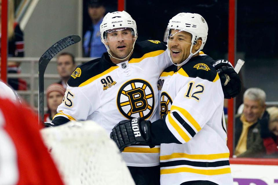 Johnny Boychuk (left) gets a hug from Jarome Iginla after his insurance goal in the third.