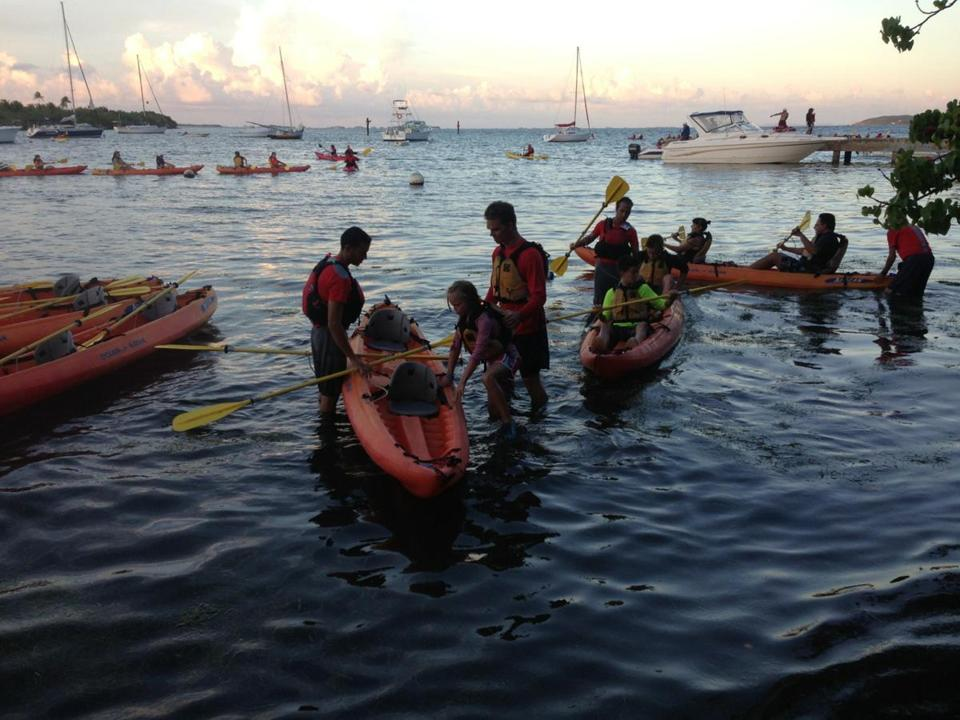 Guides assisting guests into kayaks during dispatch for Bio Bay tour in Las Croabas Harbor, Puerto Rico.