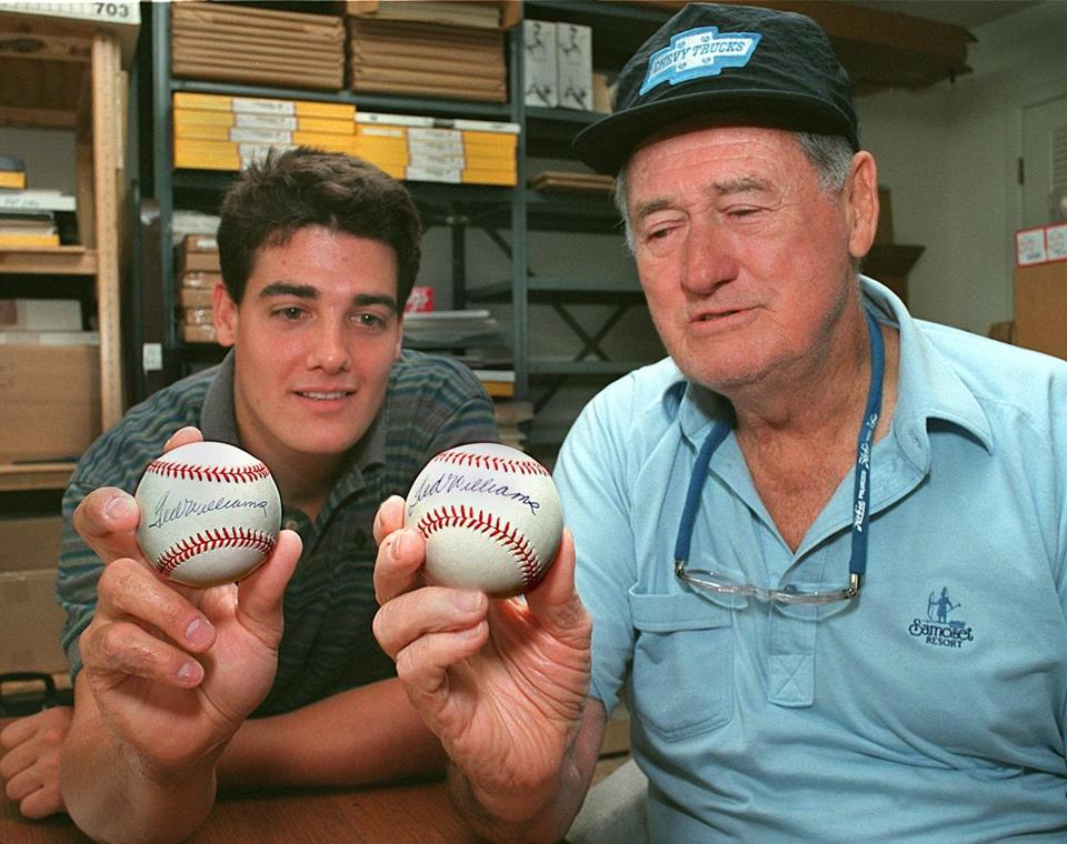 Ted Williams, right, held a baseball he autographed, while his son, John-Henry Williams, held a ball bearing a false signature.