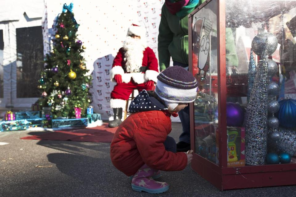 Three-year-old Georgia Steele of Hingham did not want a photo with Globe Santa, but inspected the Globe Santa donation box at the Hingham Shipyard Holiday Market.