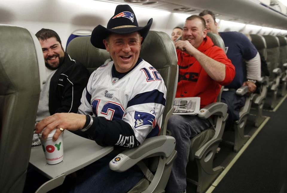 Bob Kovacev of Malden (front) got into the Texas spirit by wearing his distinctive cowboy hat on the plane to Houston as he enjoyed a laugh with Mark Capozzi (left) of Windham, N.H., and fellow New England travelers.
