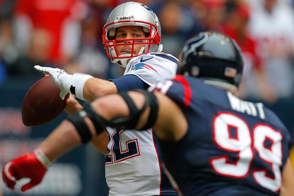 With imposing Texans lineman J.J. Watt bearing down on him, Patriots quarterback Tom Brady (2 touchdowns, 1 interception) gets off a pass during the first quarter.