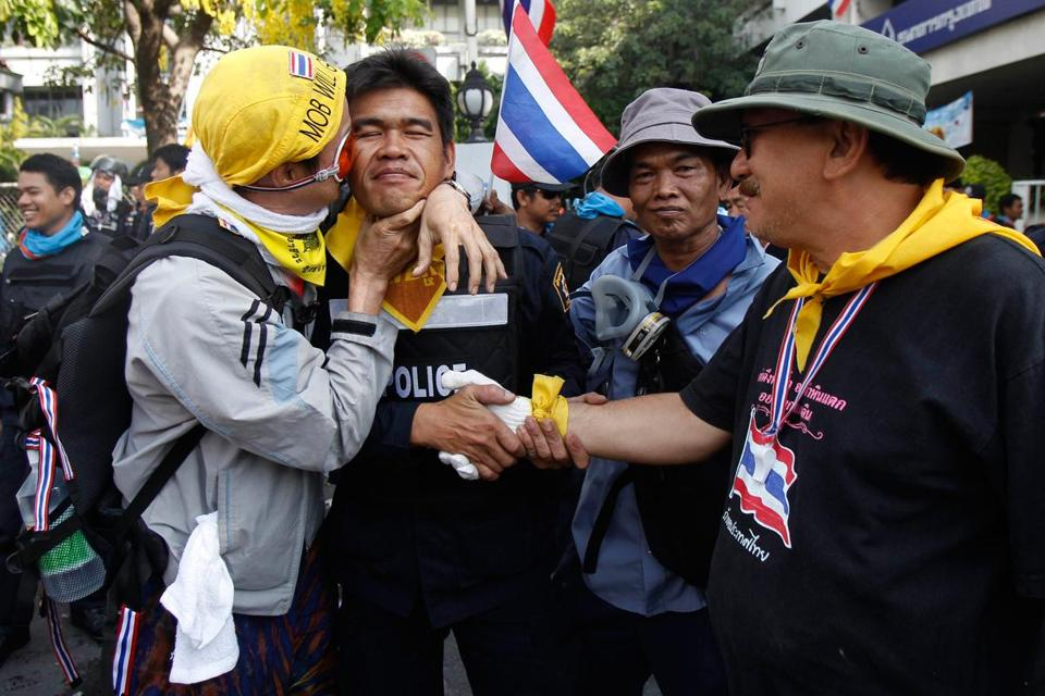 An antigovernment protester kissed a riot police officer during a rally in Bangkok Tuesday.