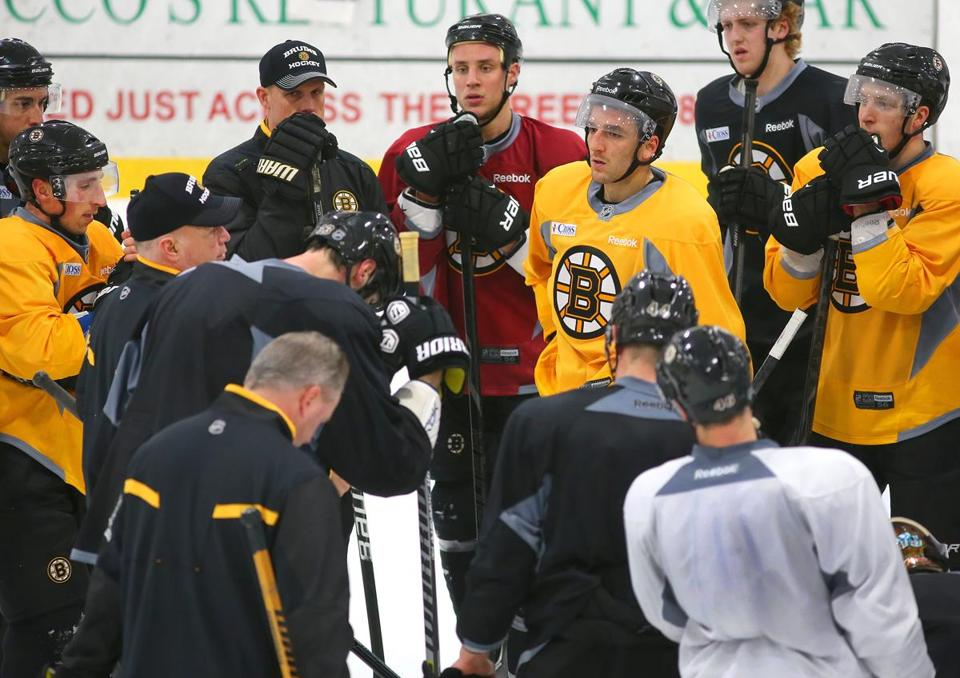 Bruins players and coaches gather around Claude Julien (left) during practice Tuesday at Ristuccia Arena.
