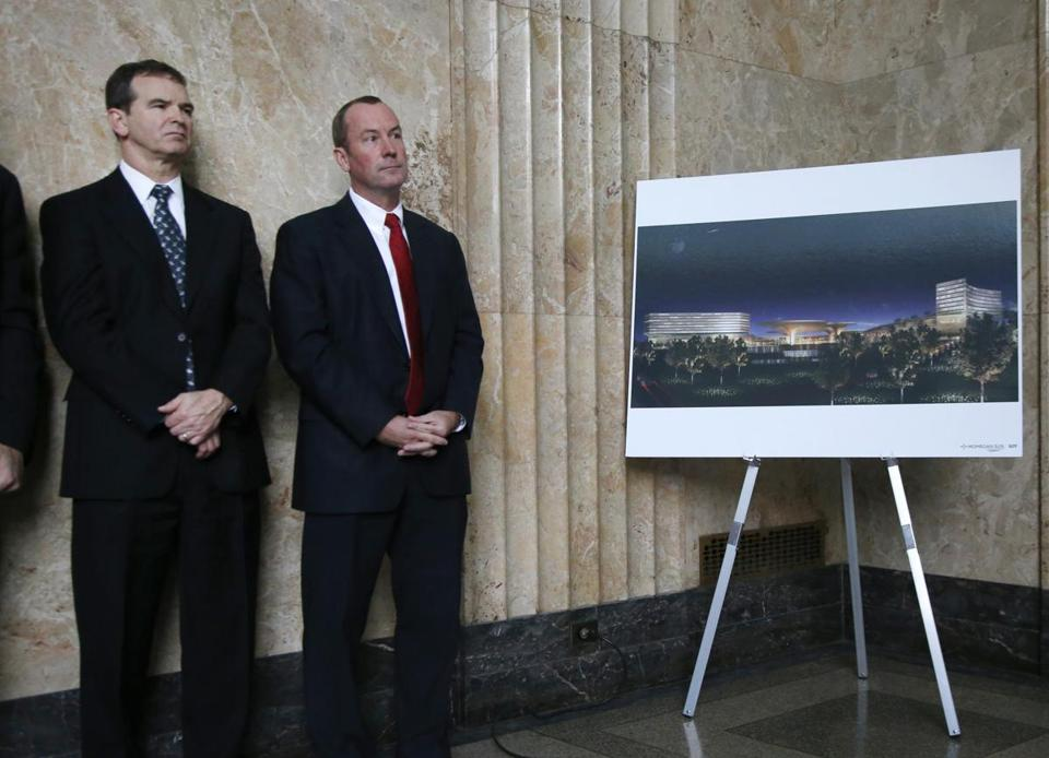 Gary Luderitz of Mohegan Gaming Advisors (left) and Chip Tuttle of Suffolk Downs at a news conference Monday in Lynn, next to a rendering of a proposed casino development.