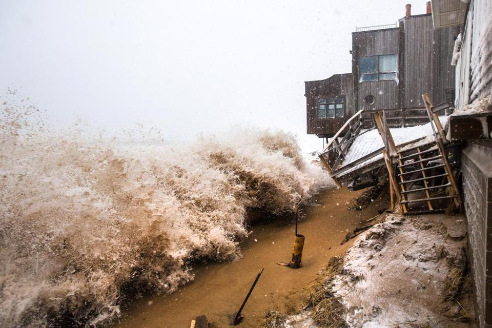 Large waves crashed over sand barriers, destroying the decks of homes along the beach on Plum Island during a storm last winter.