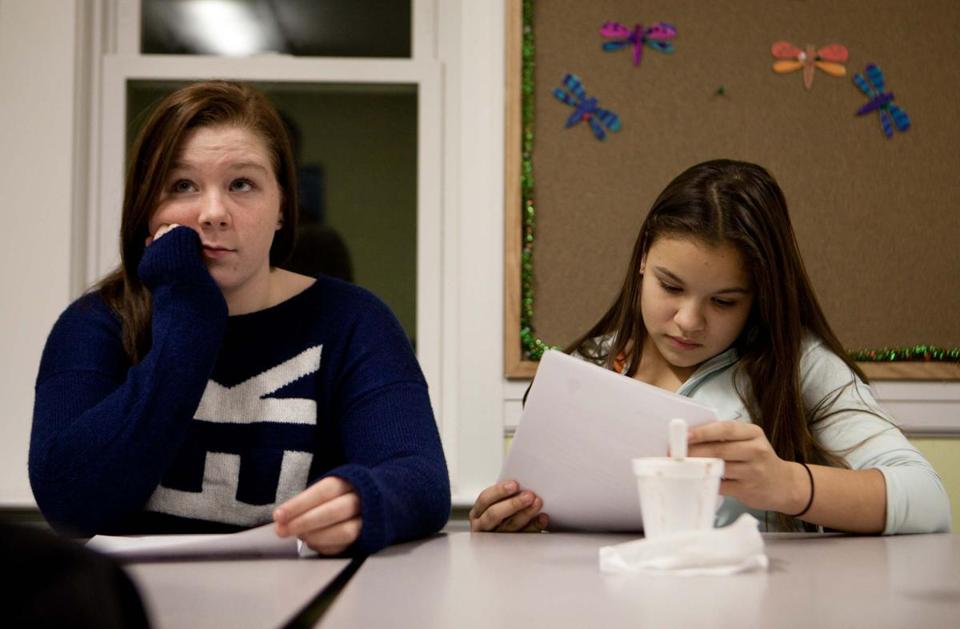 "Keefe Technical School student Erin Dowdy, 15, (left) and Framingham High School student Daniella Araujo, 14, attend a ""Moneythink"" class held at the Framingham Housing Authority community center"