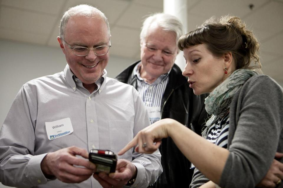 Kellian Adams Pletcher of Green Door Labs shows William Hilton (left) and James G. Shelnut a product that her com-pany is developing during a recent TechSandBox