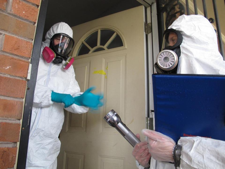 Certified industrial hygienist Gary Siebenschuh (left) and an aide got set to check a house once used as a meth lab.