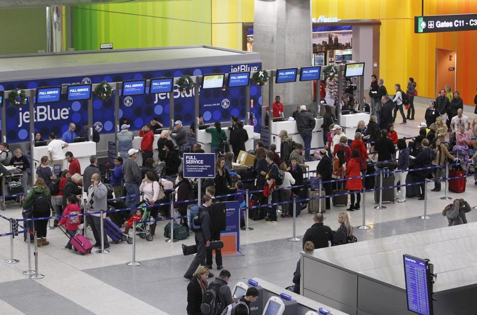 Passengers waited in a long line at Logan Airport's Terminal C on Sunday.