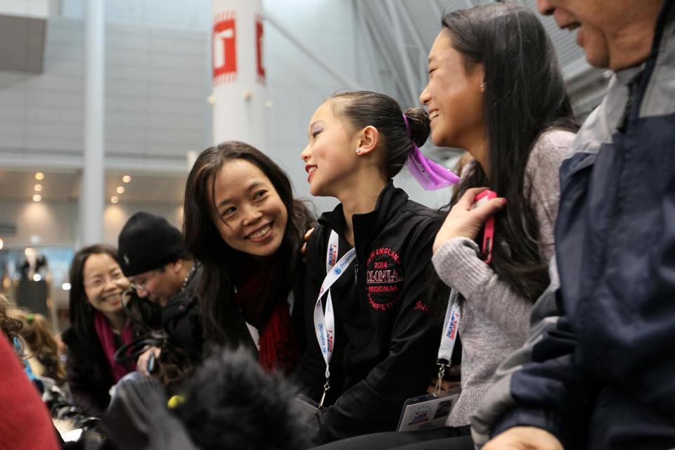 Twelve-year-old Iris Zhao (center) of Acton is flanked at a competition this week by mother May Liu (left) and sister Rose.