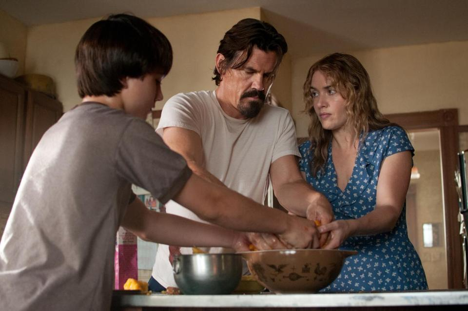 Gattlin Griffith and Kate Winslet, mother and son, make pie with an escaped convict, played by Josh Brolin.