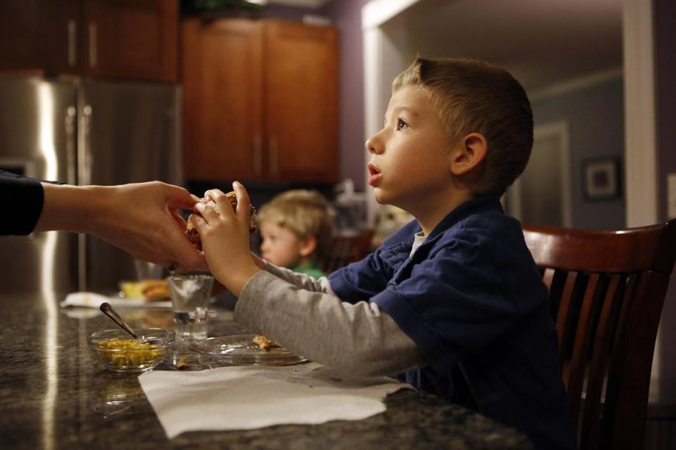 Thomas Estey was handed a hamburger on a gluten-free bun by his mother, Lora, at their West Roxbury home.