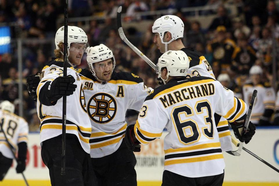 The Bruins' Patrice Bergeron (center) celebrates his third-period goal with Dougie Hamilton (left), Zdeno Chara, and Brad Marchand.