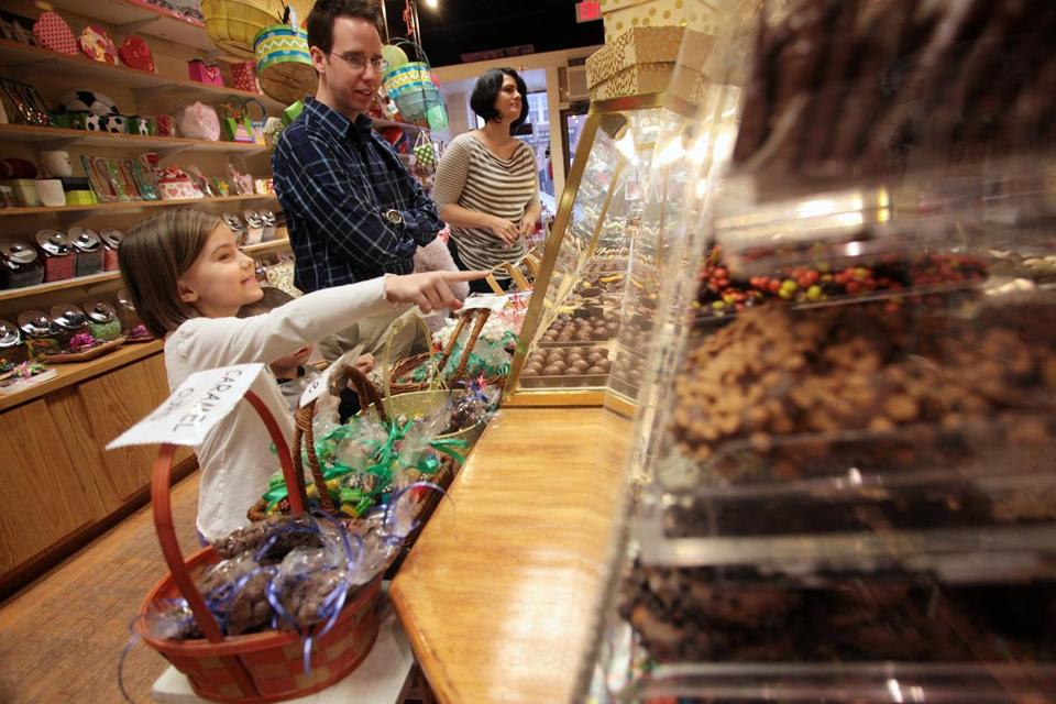 Mike Cross listens while his daughter, Natalie, 7, points out different varieties of chocolates at Sweet Mimi's in Andover.