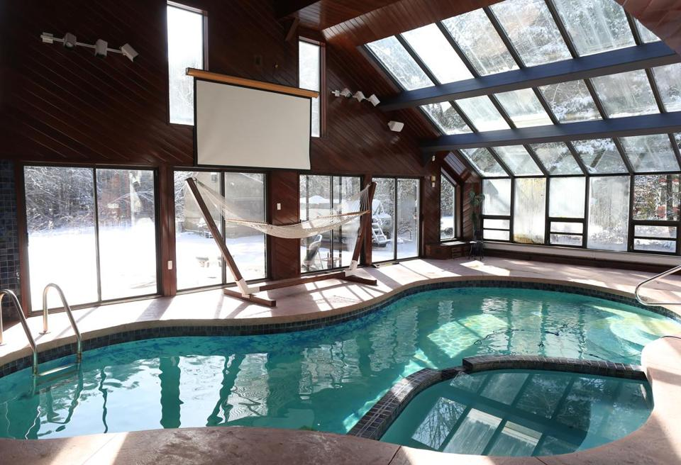 the pool room has a cathedral ceiling kitchen area and glass walls - Saltwater Hot Tub