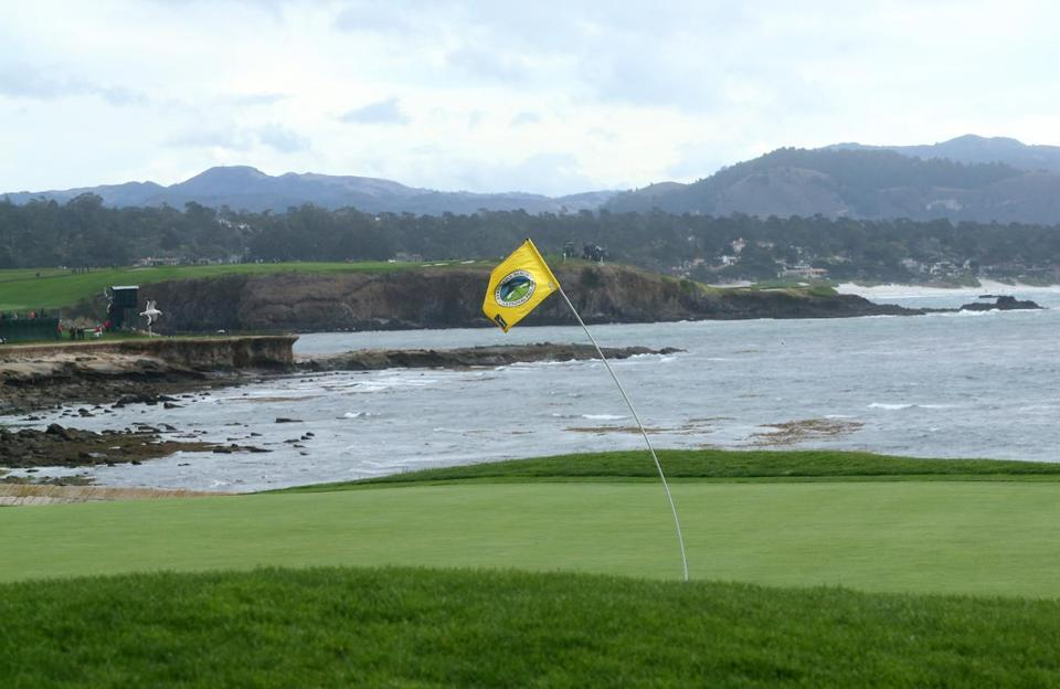 The flagstick on the 18th hole bended in the wind during a weather delay Saturday at Pebble Beach.