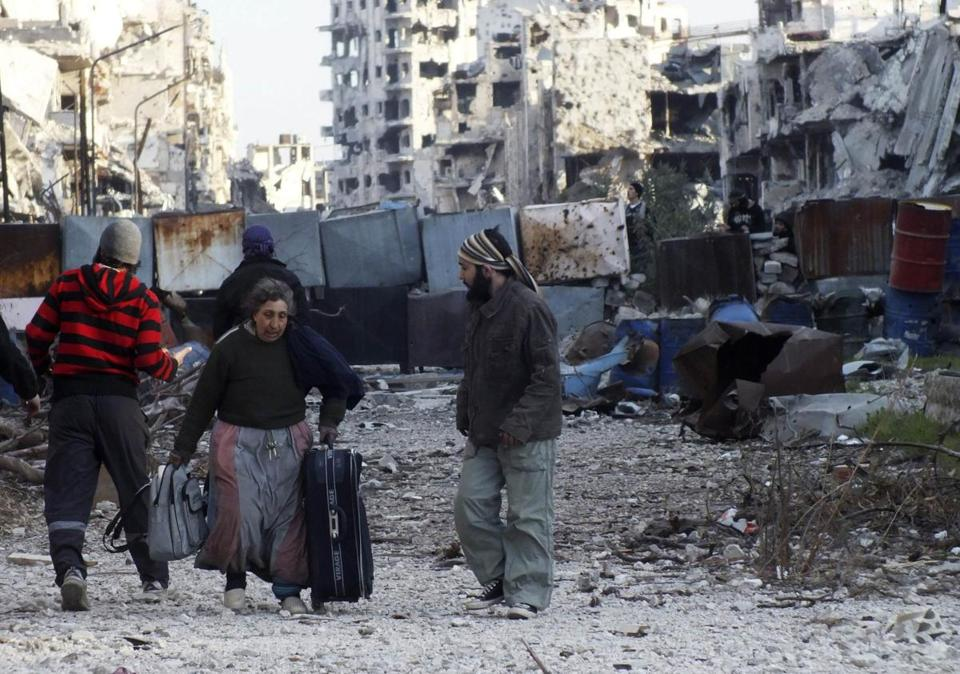 A woman carried her belongings as she walked Monday toward an evacuation point in a besieged area of Homs.