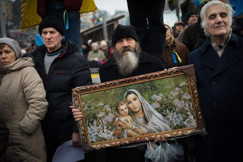 A man, with a religious painting,  joined demonstrators gathered in Independence Square in Kiev on Sunday in a mass rally against the government of President Viktor Yanukovych.