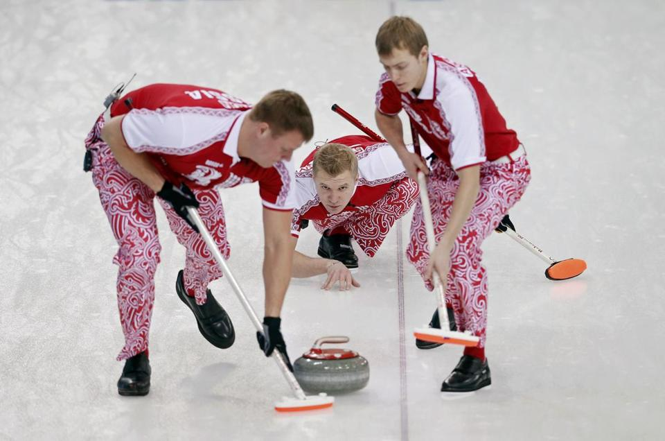 Russia's vice Alexey Stukalskiy, center, delivered a stone as Russia's Peter Dron and Evgeny Arkhipov swept during their men's curling round robin game against Britain.